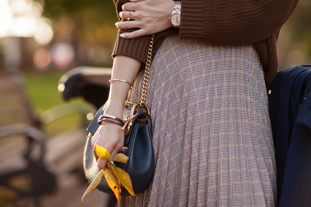 Menina elegante em um parque de outono em um suéter marrom e saia xadrez.