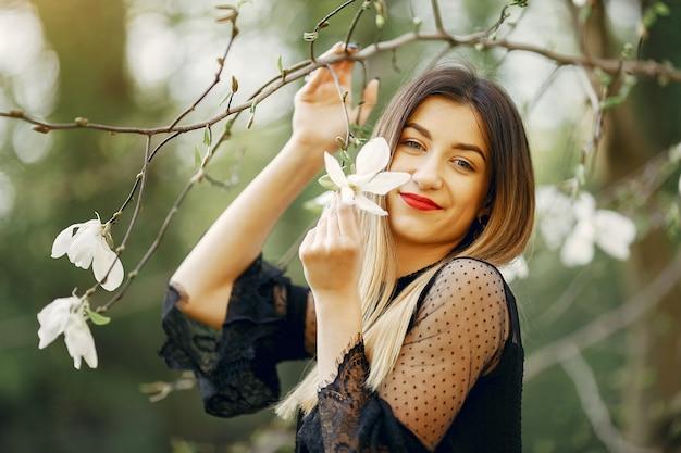 Menina elegante em um parque de primavera