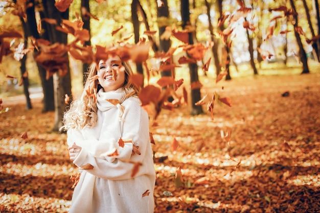 Menina elegante em um parque ensolarado de outono
