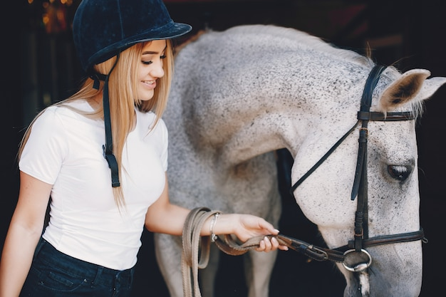 Menina elegante em uma fazenda com um cavalo