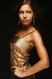 Menina elegante em vestido de ouro, fundo preto
