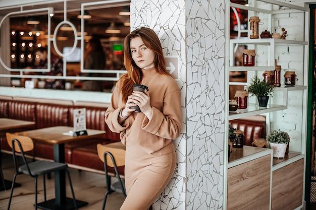 Menina elegante está bebendo café em um café. uma mulher com cabelo ruivo está de pé contra uma parede em um terno bege. interior moderno. café para viagem em copo de papelão