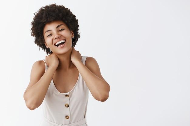 Menina elegante feliz e despreocupada posando contra a parede branca