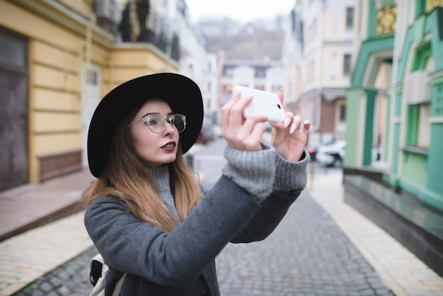 Menina elegante fotografando uma foto de rua no telefone. garota turista faz uma foto da arquitetura em um smartphone.