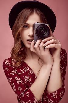 Menina elegante hipster em vestido vermelho, chapéu preto e óculos com câmera