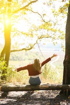 Menina elegante hipster está sentada na floresta. mulher feliz, apreciando a natureza do outono. paisagem bonita. conceito de viagens de estilo de vida. suéter vermelho escuro. folhas amarelas nas árvores. vista da colina da montanha.