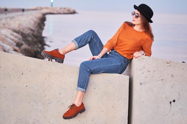 Menina elegante jovem sentado em um porto marítimo