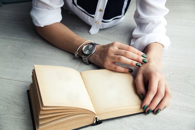 Menina elegante lendo um livro deitado no chão.