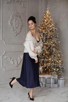 Menina elegante modelo com maquiagem e penteado perfeitos em vestido azul e aconchegante casaco de lã posando em f.