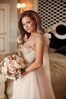 Menina elegante modelo em um vestido de noiva vintage, posando com a jovem mulher de buquê de noiva vestindo um vestido de noiva.