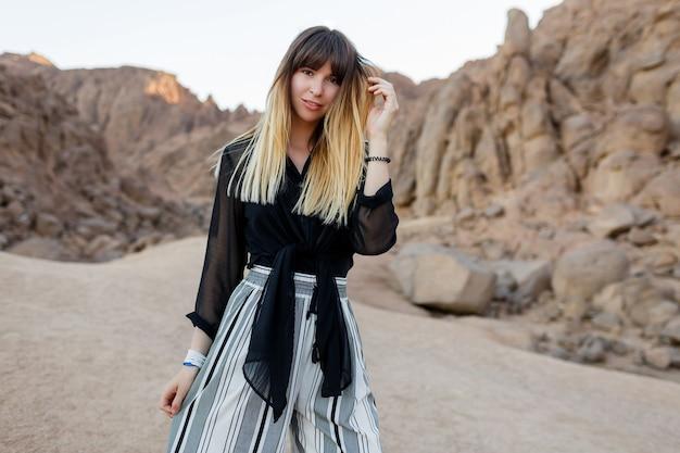 Menina elegante muito sorridente posando nas dunas de areia do deserto egípcio.