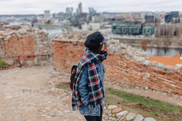 Menina elegante na caminhada de jaqueta jeans no fundo de vilnius