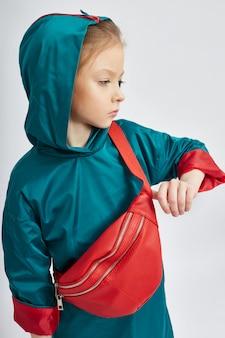 Menina elegante na moda em uma capa de chuva com capuz.