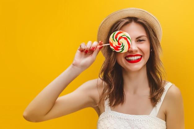 Menina elegante nova em um chapéu de palha com um pirulito colorido em um fundo amarelo