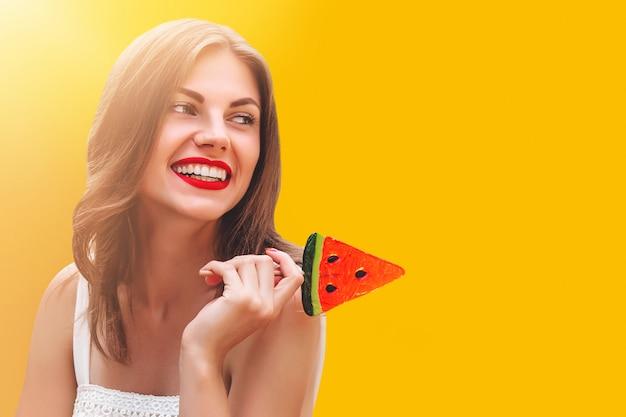 Menina elegante nova em um chapéu de palha com um pirulito doce em um fundo amarelo