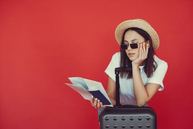Menina elegante posando com equipamento de viagem em uma parede vermelha