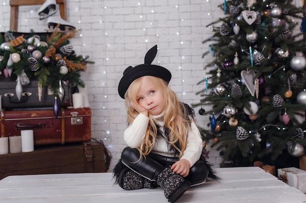 Menina elegante posando perto da árvore de ano novo em antecipação ao natal