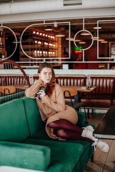 Menina elegante se senta em um café à mesa e bebe café. café para viagem em copo de papelão. mulher ruiva em um terno quente bege em um ambiente aconchegante. interior moderno. passatempo calmo e agradável.