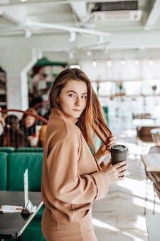Menina elegante se senta em um café e bebe café. café para viagem em copo de papelão. mulher com cabelo ruivo em um terno quente bege em um ambiente aconchegante. interior moderno. passatempo calmo e agradável