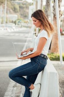 Menina elegante segurando um laptop ao ar livre