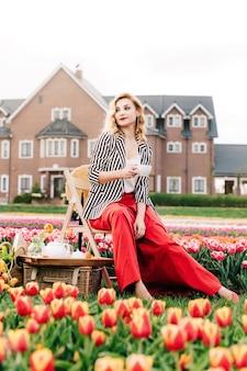 Menina elegante segurando uma xícara de chá e fazendo um piquenique no campo de tulipas