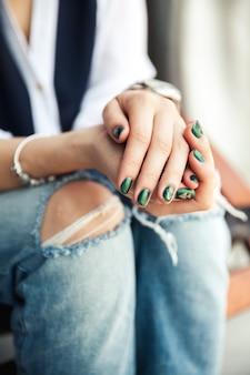 Menina elegante sentada em jeans rasgados e esmalte verde moderno, relógio, pulseira. moda, estilo de vida, beleza, roupas. e