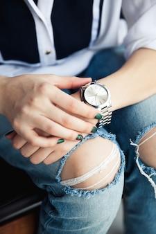 Menina elegante sentada em jeans rasgados e manicure moderna verde, relógio de prata da ponte, pulseira. moda, estilo de vida, beleza, vestuário. e