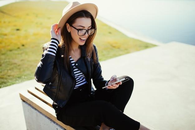 Menina elegante sentada no parque perto do lago da cidade em um dia frio e ensolarado de verão, vestida com roupas pretas
