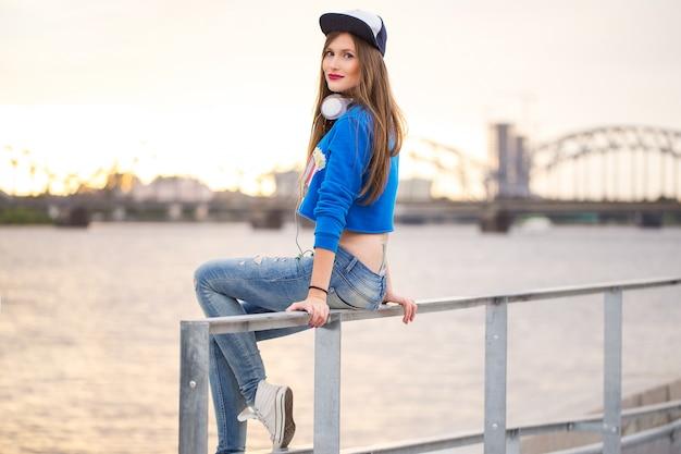 Menina elegante, sentado em um corrimão