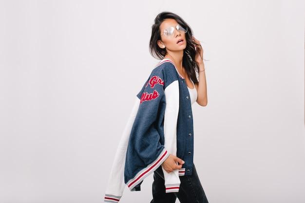 Menina elegante usa óculos grandes da moda, posando e brincando com o cabelo brilhante. jovem europeia em acessórios elegantes, segurando a jaqueta esporte azul isolada.