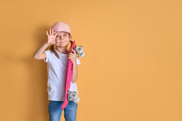 Menina elegante, vestindo camiseta branca, jeans azul e boné rosa, segurando o skate sobre fundo amarelo