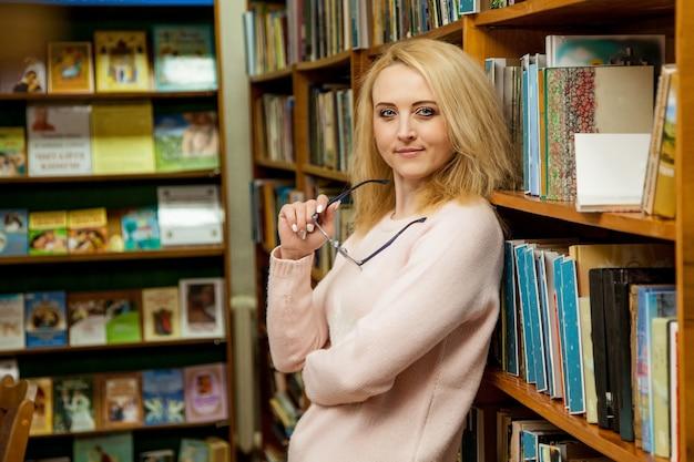Menina, em, biblioteca, com, óculos, em, mão