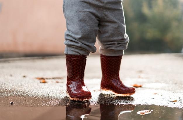 Menina em botas de chuva vermelhas jogando na poça depois da chuva