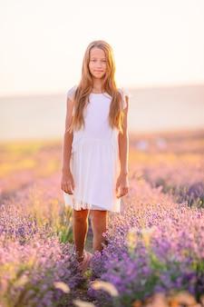 Menina em campo de flores de lavanda em vestido branco