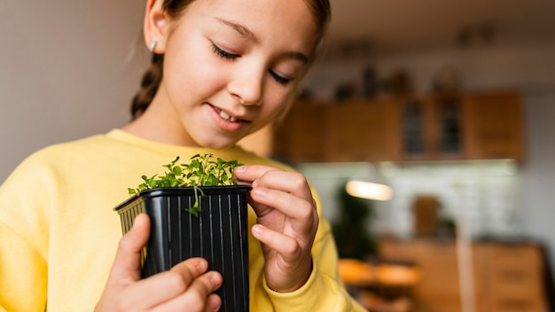 Menina em casa com uma pequena planta