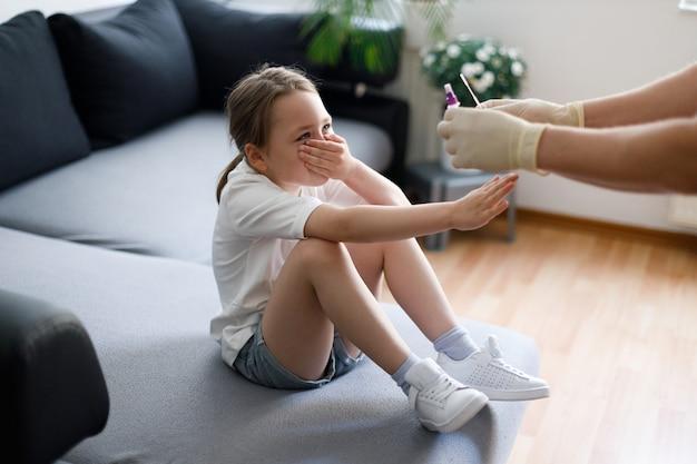 Menina em casa durante a coleta de amostra de teste de muco nasal do nariz realizando procedimento de teste de vírus respiratório mostrando covid-19