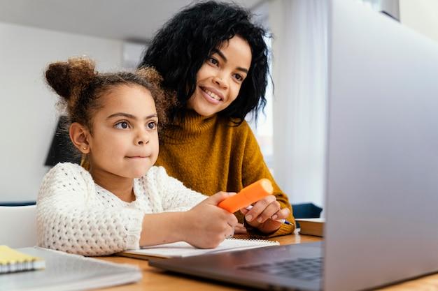 Menina em casa durante a escola online com a irmã mais velha