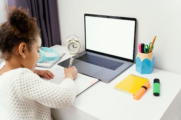Menina em casa durante a escola online usando laptop