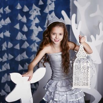 Menina em decorações de natal. retrato de uma linda menina com cabelo longo cacheado e coroa