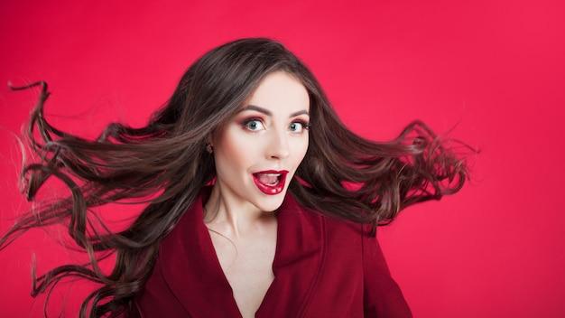 Menina em estado de choque na parede rosa. jovem mulher bonita com cabelo preso.