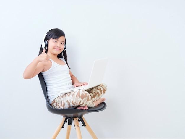 Menina em fones de ouvido com o laptop.
