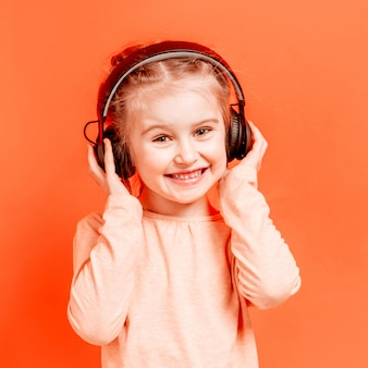 Menina em fones de ouvido sobre parede rosa