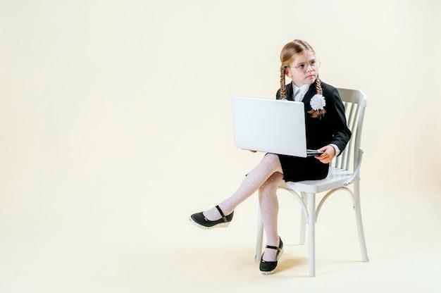 Menina em idade escolar parece em um laptop sobre um fundo claro, o vício em internet