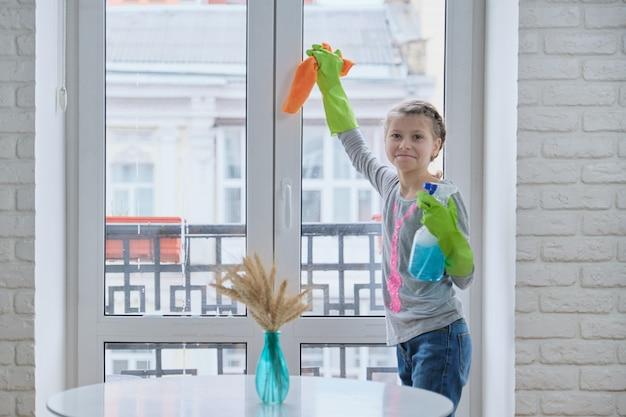 Menina em luvas com detergente spray com pano de limpeza de janelas