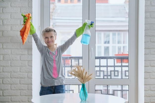 Menina em luvas com spray de detergente e pano para limpar a casa, lavar janelas, primavera, copiar espaço