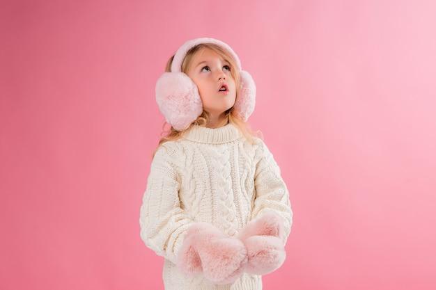 Menina em luvas cor de rosa e fones de ouvido em uma parede rosa