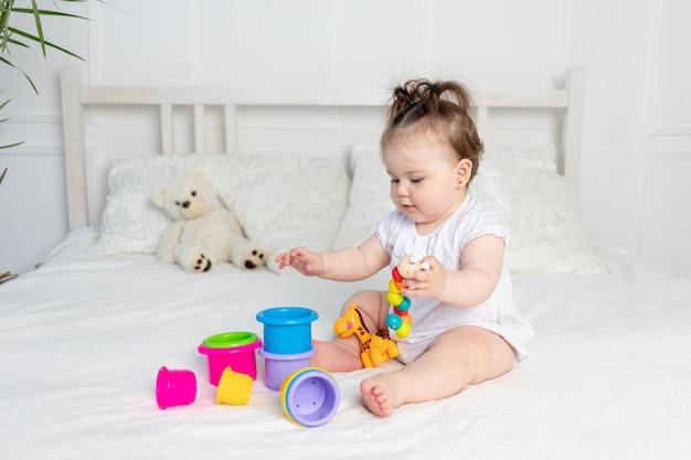 Menina em macacão branco brincando com brinquedos coloridos na cama em casa em um quarto bem iluminado