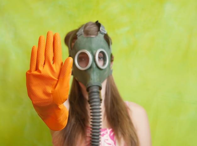 Menina em máscara de gás apontando stop