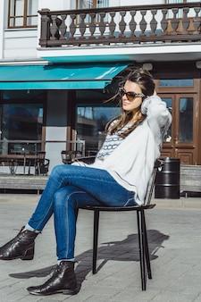 Menina em óculos de sol em um café da rua