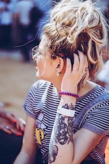 Menina em óculos de sol vintage com retrato de tatuagem close-up na rua durante um piquenique com amigos. chill girl